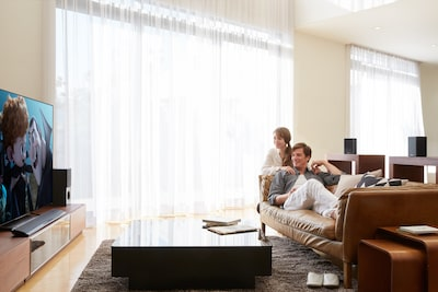 Two people are watching TV with wireless surround system in living room.