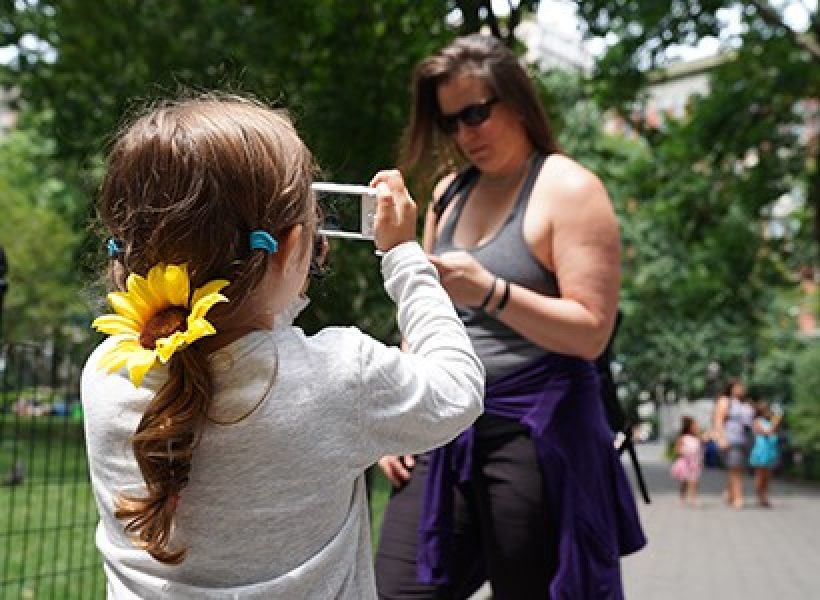 Young girl taking a picture of a woman