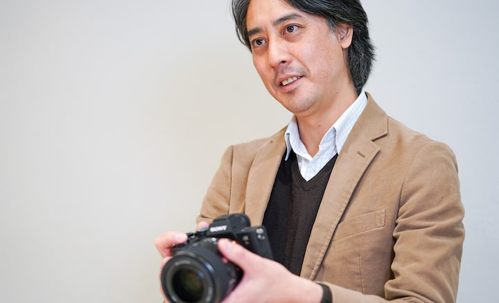 The Optical Design Lead holds the FE 50mm F1.2 lens while delivering an explanation