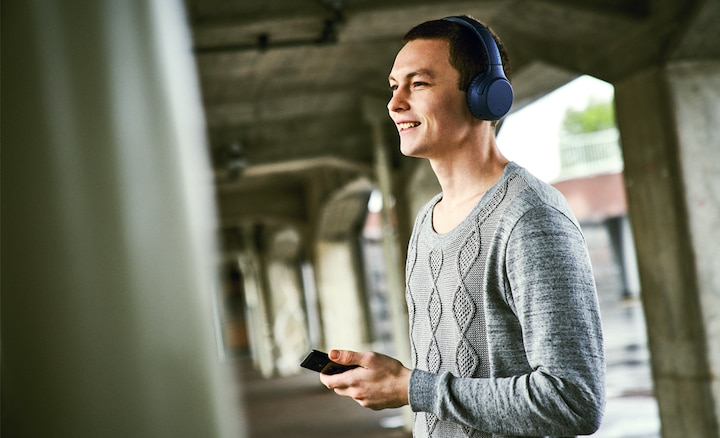 Lifestyle shot of man making hands-free call using WH-XB700 headphones