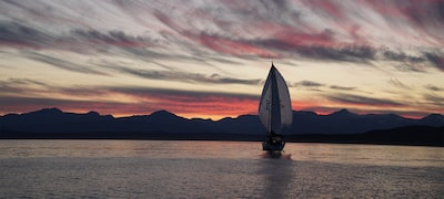 Image showing sailboat on lake against sunset with patterned sky and darker hills