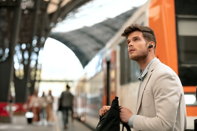 Lifestyle image of man waiting at station wearing WF-1000XM3 headphones
