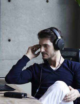 Image of a man listening to music with headphones