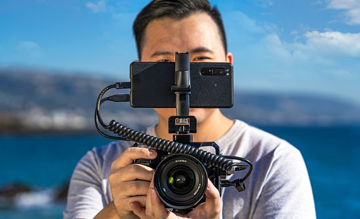 Image of Jason Vong using camera with the Xperia PRO mounted on top.