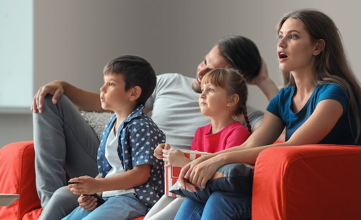 Family of four intently watching TV on red sofa eating popcorn