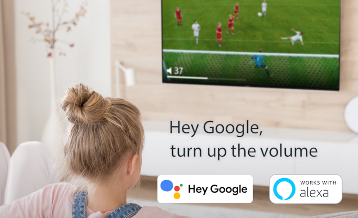 Woman watching soccer on Sony TV using voice control with Google Assistant, also with . OK Google and Alexa logos