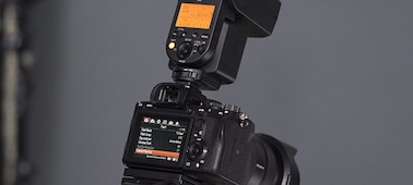 Rear view of the camera with an external flash mounted on top
